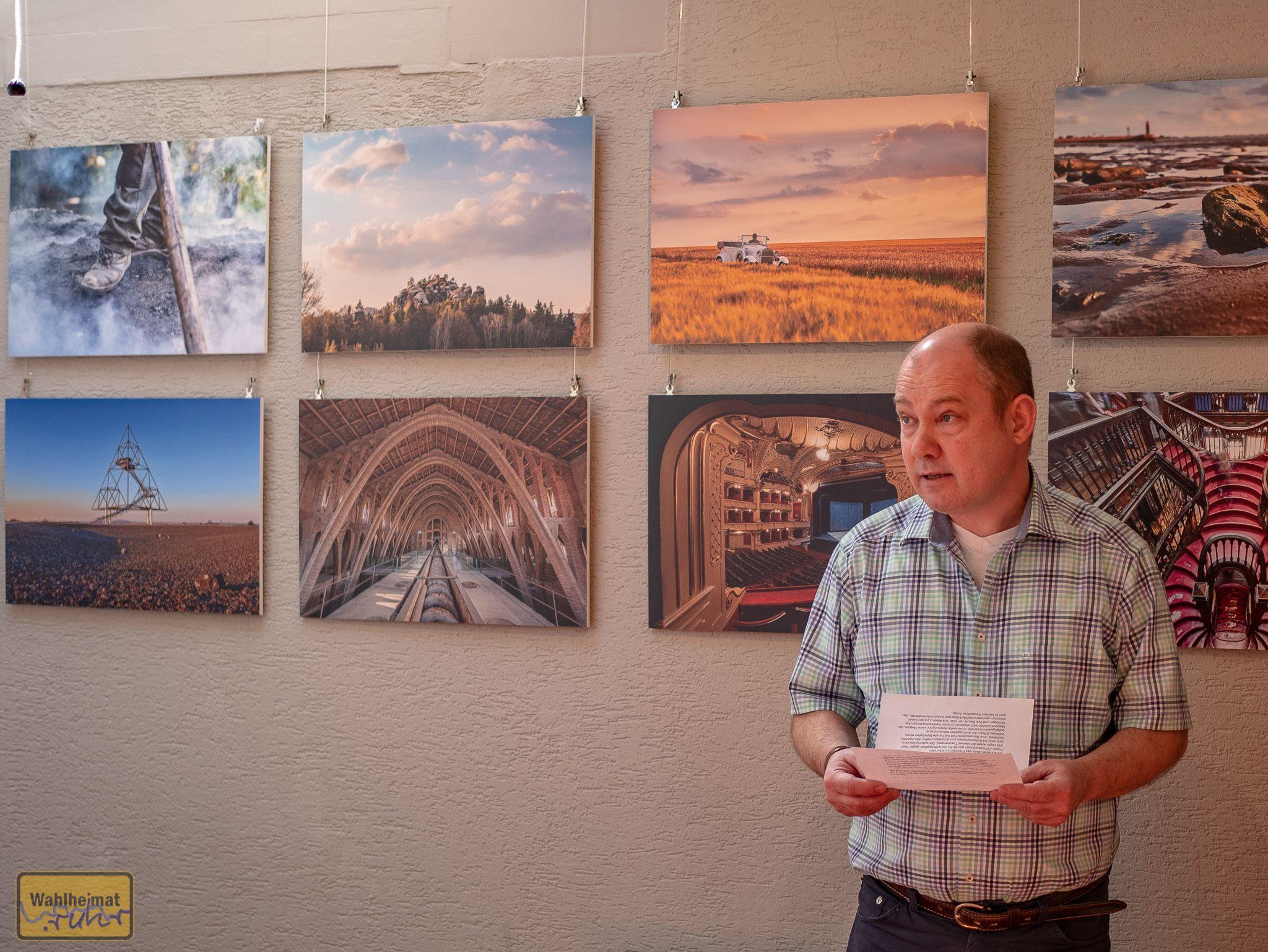 Dr. Jörg Schmitz eröffnet die Ausstellung. Im Hintergrund sieht man z.B. auch Motive aus dem Siegerland und natürlich dem Ruhrgebiet.