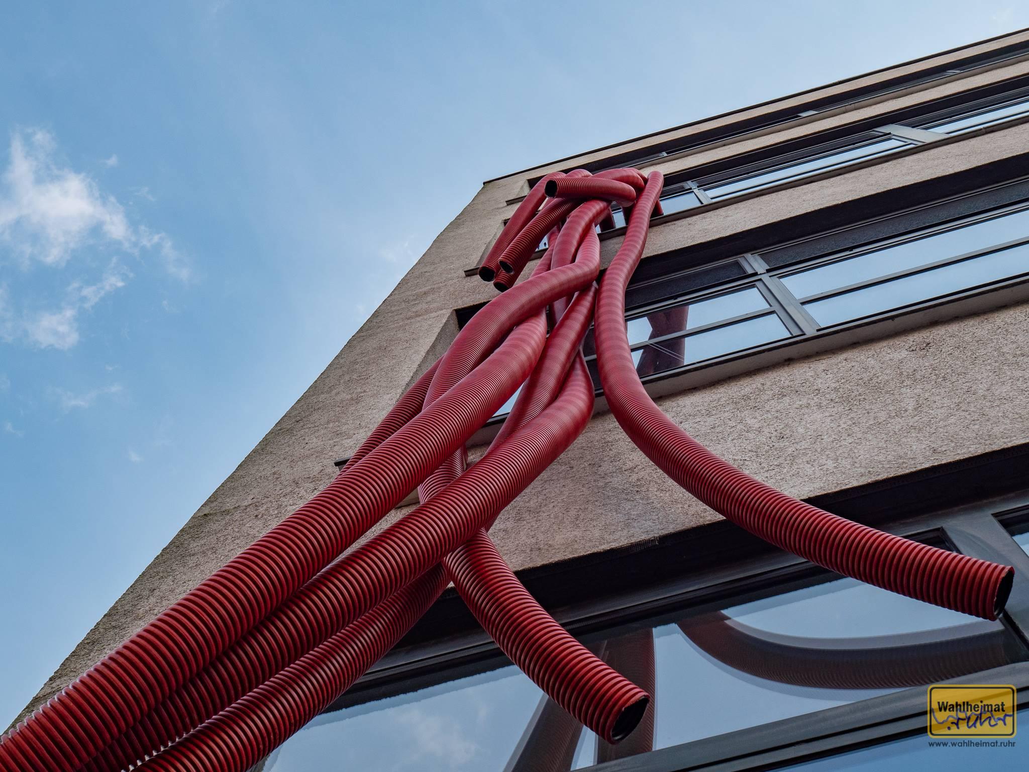 Ludwig Mies van der Rohe baute übrigens nur einen einzigen Industriebau: an dessen Fassade kann man derzeit seiner Originalstimme in langen, roten Rohren lauschen.