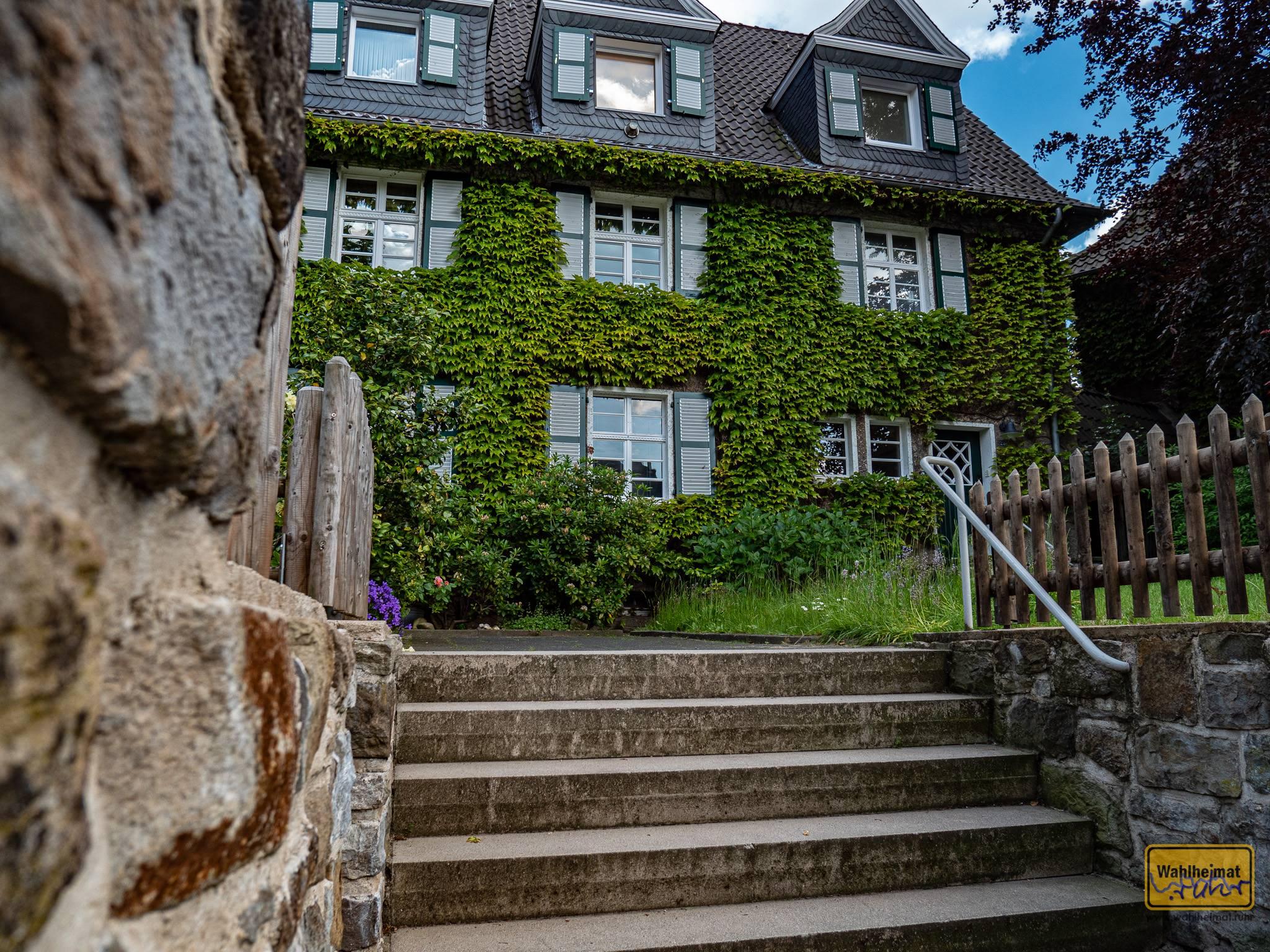 Typisch für so viele Fassaden schlingt sich auch hier Grün an der Hauswand empor.