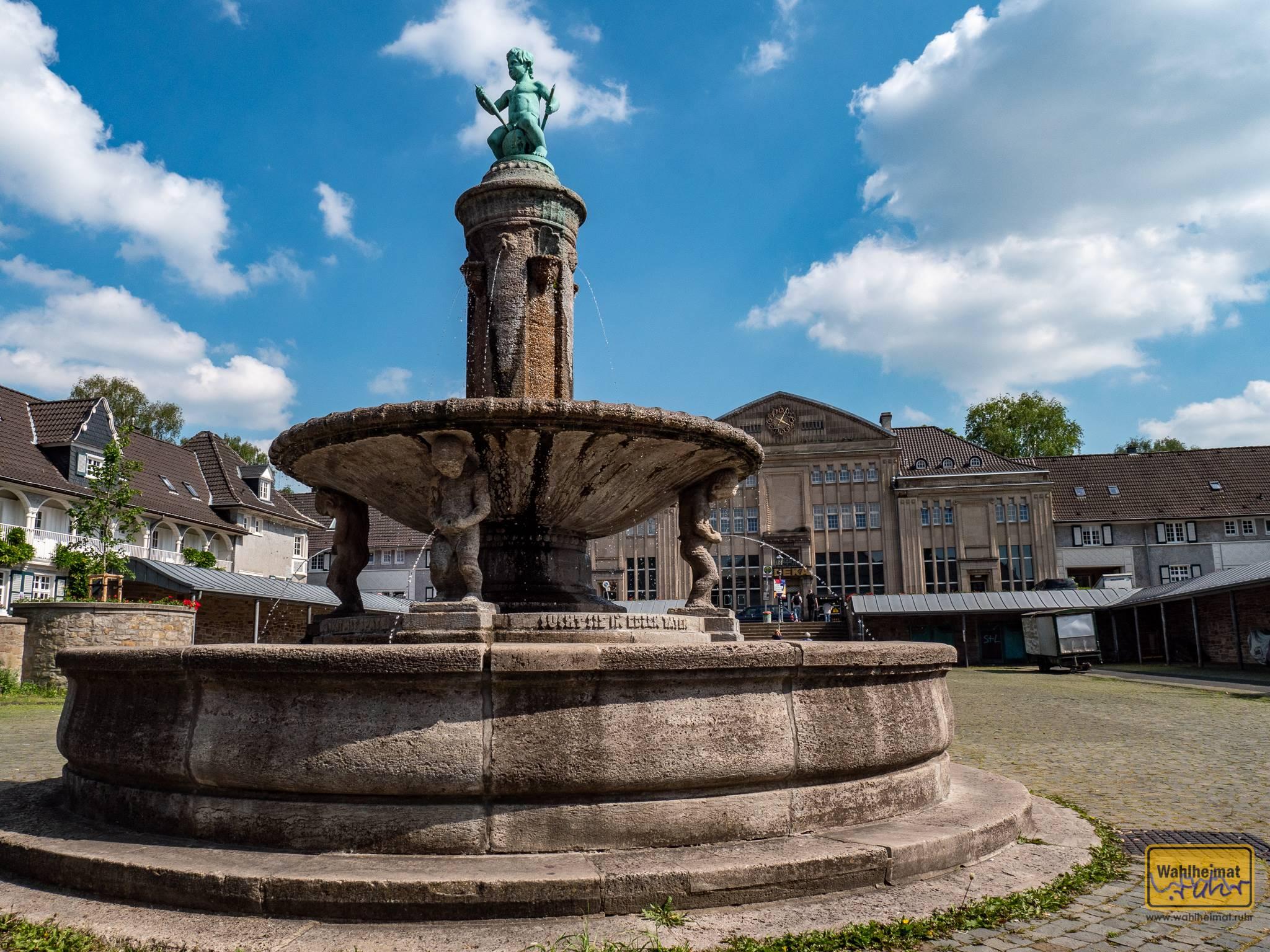 """Auf der Margarethenhöhe gibt es einen schönen Marktplatz - der dort befindliche Brunnen ist sowas wie ein Wahrzeichen und wird auch als Schatzgräberbrunnen betitelt. Die Inschrift lautet """"Grabt Schätze nicht mit Spaten, sucht sie in edlen Taten."""""""